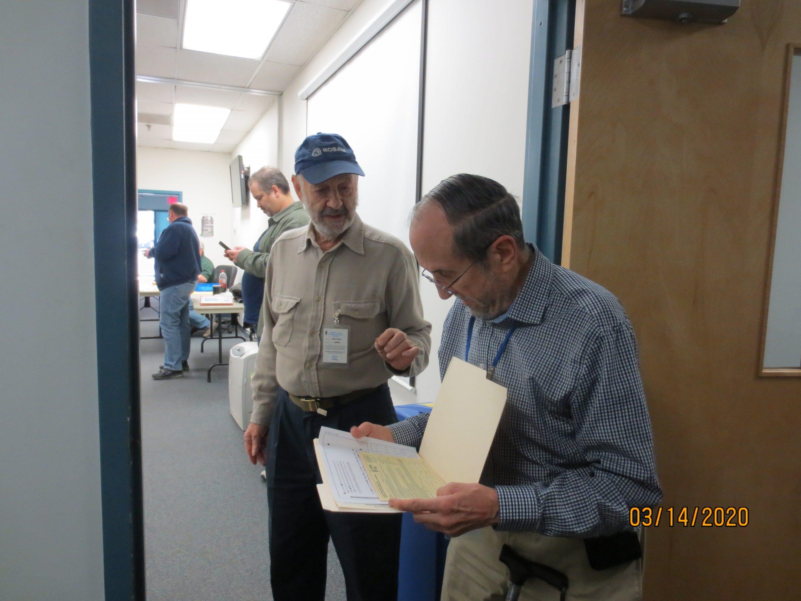 Luther, WA3FMO, checks exam paper work with AL, KB4BHB